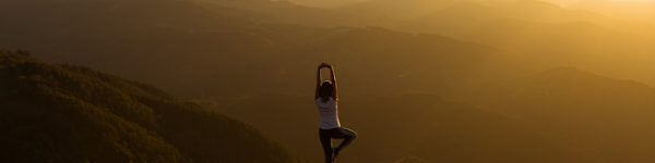 Woman stretching on a mountain top at sunris